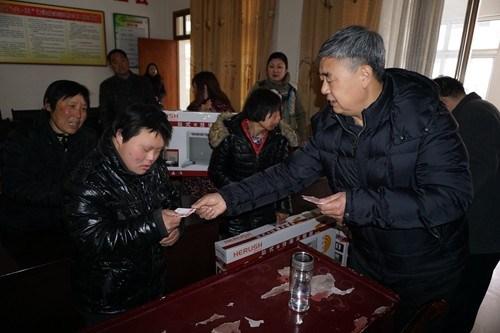 图为固始县政府县长级干部黄永涛向困难残疾群众发放慰问金