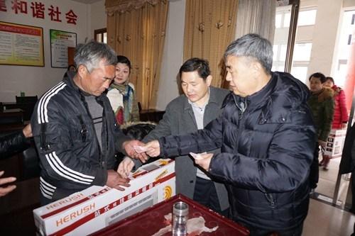 图为固始县政府县长级干部黄永涛向困难残疾群众发放慰问品