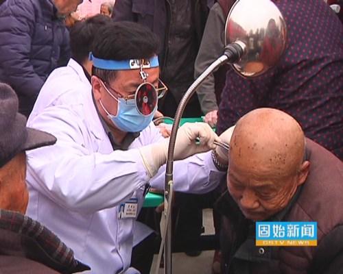 图为医生为听力障碍老人检查听力