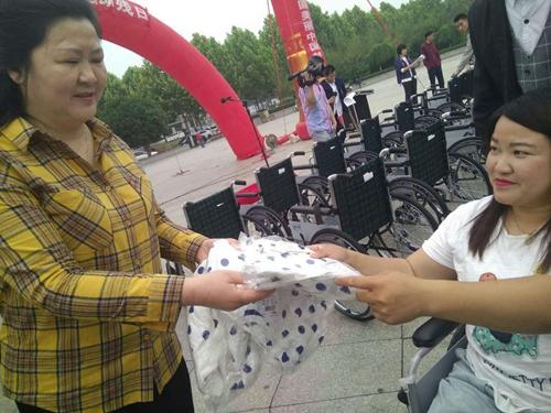 图为副县级干部余学琴与受赠女式夏装残疾人交流