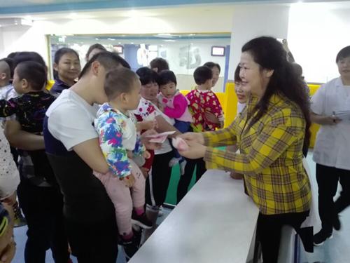 图为副县级干部余学琴看望残疾脑瘫儿童