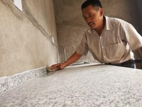 图为秦程军擦拭改造的厨房低位灶台