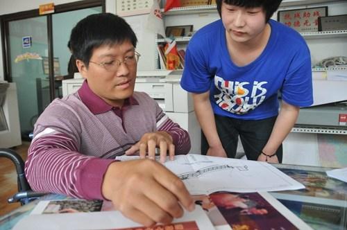 图为残疾人代表姜庆伟在指导员工