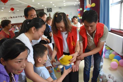 圖為:宜陽縣殘聯康復科科長梁愛娟為殘疾兒童發放玩具