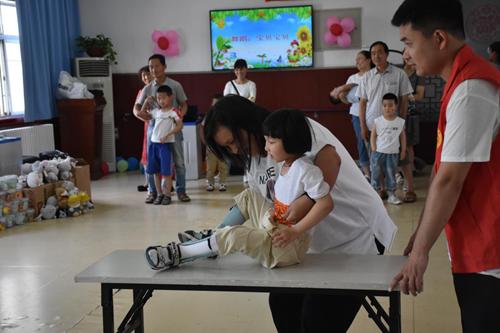 圖為:宜陽縣殘聯工作人員與殘疾兒童一起玩游戲
