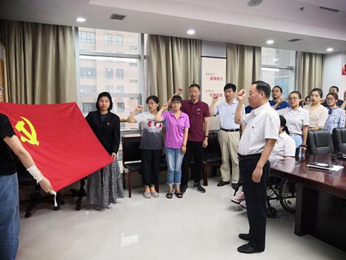 图为:残联党支部书记带领党员重温入党誓词。