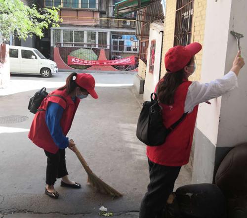 图为: 北京赛车pk志愿者在社区打扫卫生,铲除小广告