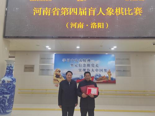 图为:省残联理事林济策为获得冠军的周口选手李明超颁奖并合影