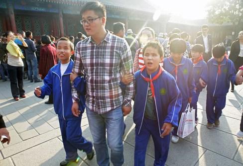 图为盲童在老师和志愿者的带领下游览恭王府