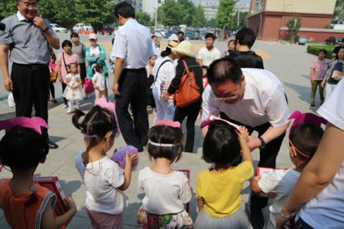 图为市政府副市长沈运田给小朋友送上节日礼物