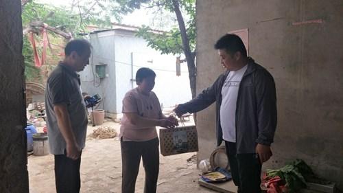 图为:南乐县残联深入帮扶村为贫困残疾人送去粽子