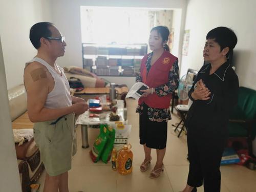 图为市残联副理事长张湘鄂向残疾人家属了解情况