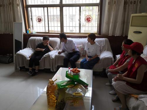 图为市残联党组成员、副调研员赵学恩与青年残疾人交谈