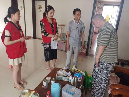 图为市残联调研员朱家广鼓励残疾人坚持康复训练战胜病魔