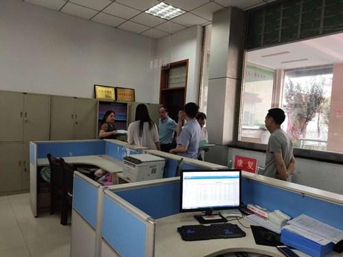 图为济源市领导到范县残联办公楼查阅邻里照护资料