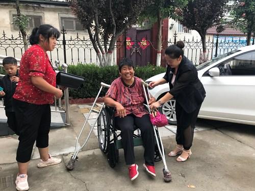 图为双下肢残疾人喜领轮椅