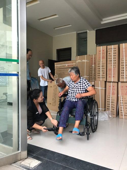 图为残联工作人员为残疾人演示轮椅使用情况