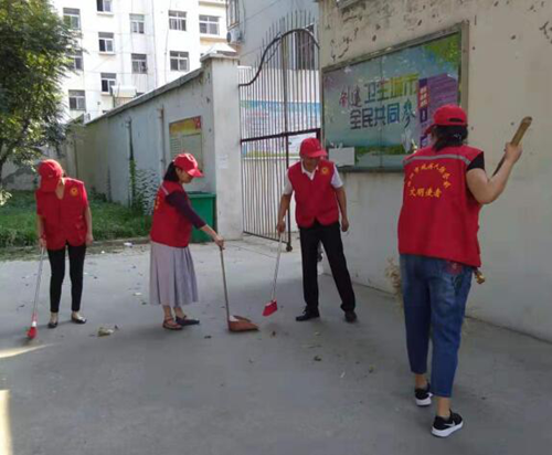 图为:党员志愿者开展清洁家园活动,助力全国文明城市创建