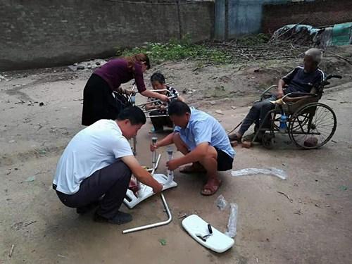 图为县残联工作人员上门发放沐浴凳并为残疾人安装