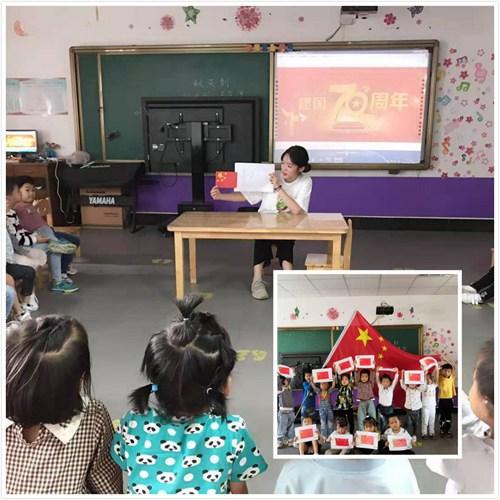图为老师给孩子们讲解五星红旗的制作步骤