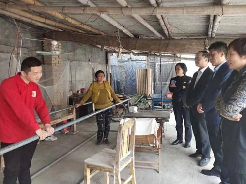 图为王改印副主任、孙献玲理事长与重度残疾人史乐乐的照护人交流