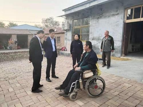 图为王改印副主任、孙献玲理事长与重度残疾人于自杰交谈,了解本人的照护情况