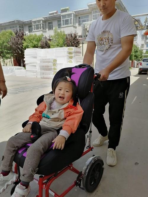 图为特殊孩子坐上了新的儿童轮椅