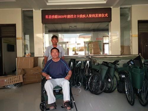 图为贫困肢残人士适配了新的轮椅