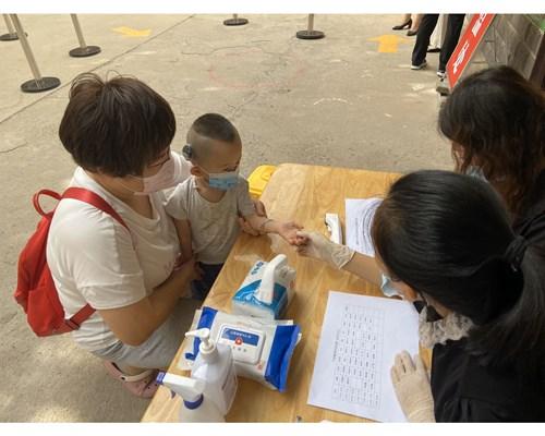 图为 中心教师对幼儿进行严格晨检,一摸二看三问四查,排除手足口等疾病隐患