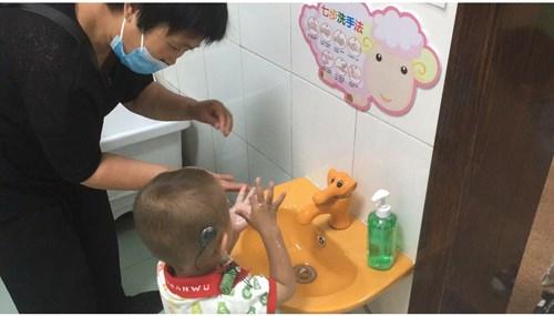 图为家长及幼儿进入个训室前按照七步洗手法进行手部卫生的清洁消毒