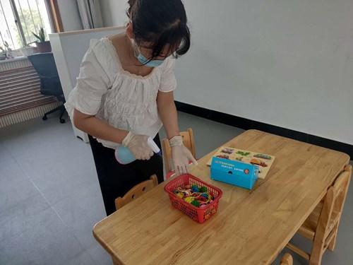 图为课程结束后,教师们严格按照要求将玩具、教具、桌面、 椅子、地面、门把手等孩子所接触的物品进行清洁消毒(1)