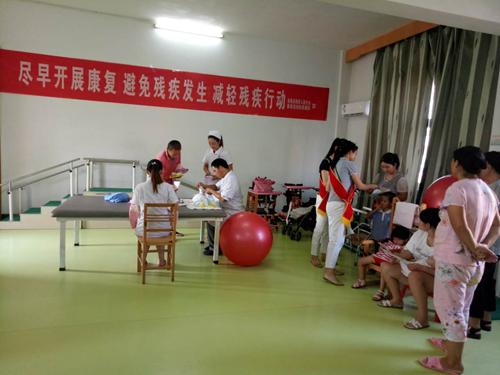 图为:残疾人志愿者为脑瘫儿童家长讲解康复知识