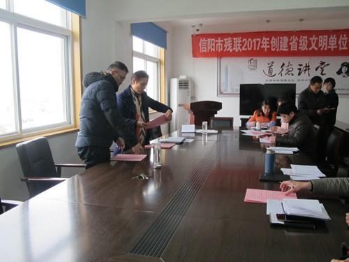 图为 市残联党组书记、理事长吴蕾与各科室负责人签订责任书