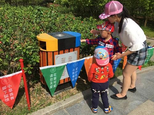 图为活动期间教导孩子垃圾丢进垃圾桶