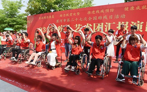 图为残疾人艺术团成员与学生志愿者一起表演手语舞蹈《感恩的心》