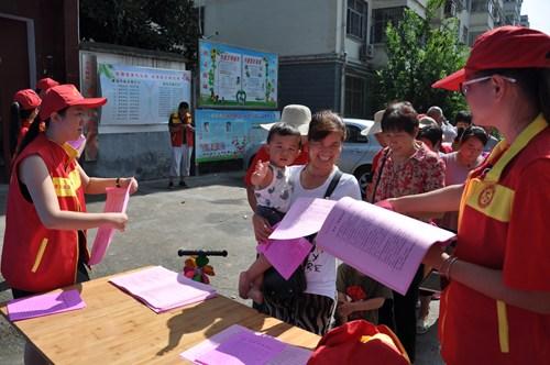图为党员志愿者向社区群众和环卫工人发放宣传资料及清洁用品