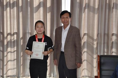 图为杨保录副理事长向获奖运动员颁发荣誉证书