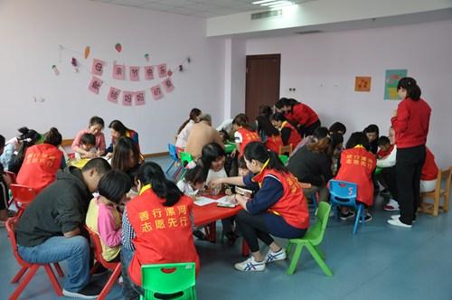 图为市残联志愿者和家长与孩子们一起做活动
