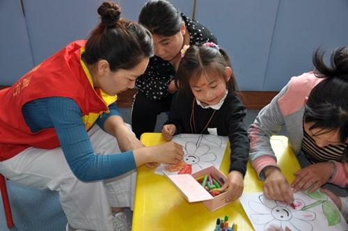 图为志愿者手把手教孩子作画