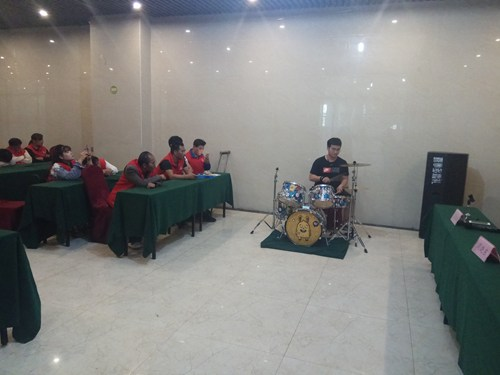 图为老师对学员进行器乐理论培训