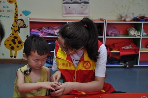 图为志愿者手把手教残疾孩子包粽子