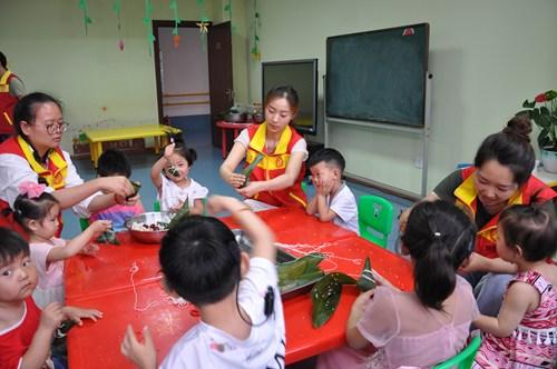 图为志愿者与孩子们自己DIY手工粽子