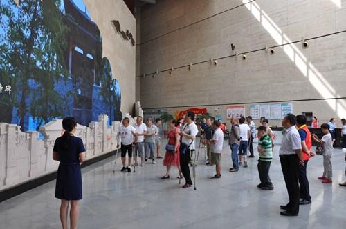 图为展览馆讲解员向残疾朋友介绍漯河历史文化
