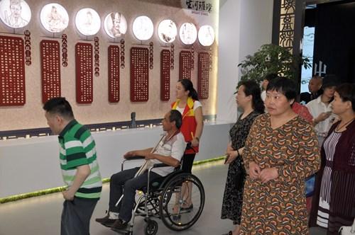 图为市残联志愿者为残疾朋友讲解漯河历史人物事迹