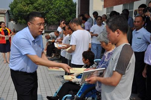图为市残联党组副书记、副理事长贾志恒为残疾人发放书籍