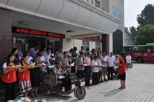图为残联志愿者领读《习近平新时代中国特色社会主义思想学习纲要》