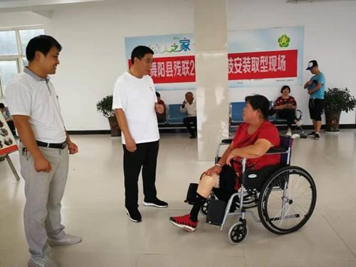 图为县残联理事长和假肢取型患者交谈