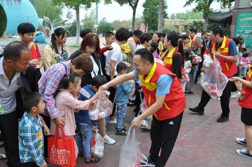 图为志愿者为孩子们发放准备好的小零食