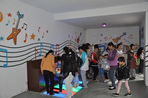 """图为孩子和家长体验""""怪街""""里面的音乐作坊"""