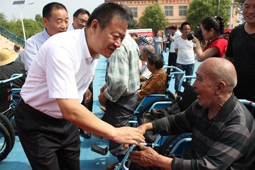 图为:市政府副市长、市残工委主任邓志辉看望接受捐赠轮椅的残疾人